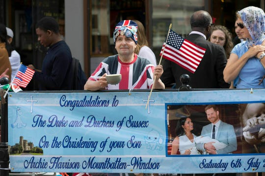 Royal superfan John Loughrey holds a sign in celebration of the royal christening of Archie, the son of Britain's Prince Harry and Meghan, Duchess of Sussex, outside Windsor Castle in England, Saturday.