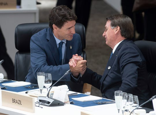 In this Friday, June 28, 2019 photo, Canadian Prime Minister Justin Trudeau shakes hands with Brazilian President Jair Bolsonaro before the start of a plenary session at the G20 Summit in Osaka, Japan.
