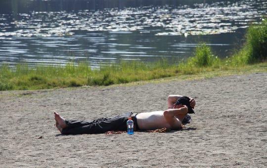 A man suns himself at Goose Lake Friday, July 5, 2019, in Anchorage, Alaska.