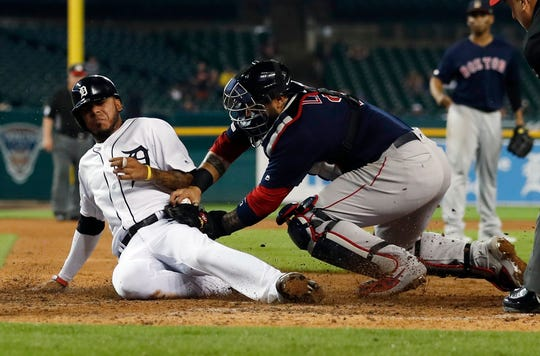 Detroit Tigers' Harold Castro, left, safely beats the tag of Boston Red Sox catcher Sandy Leon to score during the sixth inning on Friday.
