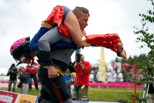 People take part in the wife carrying race, a 278-yard obstacle course, during the 24th world championships in Sonkajarvi, Finland, Saturday.