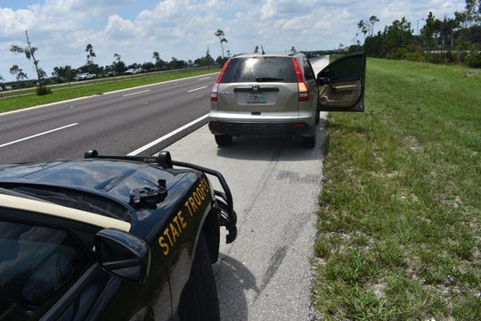 Florida Highway Patrol troopers arrest a Lehigh Acres woman after another driver reported seeing her holding a gun while in traffic.