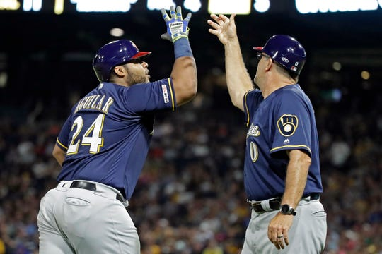 The Brewers' Jesus Aguilar rounds third to greetings from third base coach Ed Sedar after hitting a two-run home run during the eighth inning.