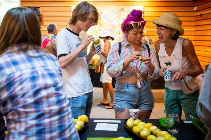 From left to right, Brandon Counter, Priscilla Tylinski, and Jan-Marie Bohannon taste passion fruit during Tasting the Tropics at Naples Botanical Garden in Naples on Saturday, July 6, 2019. The event offered tropical fruit tastings, demonstrations, and tours of the garden's edible plants.