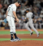 Tampa Bay Rays reliever Emilo Pagan, foreground, smooths the mound after giving up a solo home run to New York Yankees pinch hitter Aaron Hicks, back right, during the eighth inning of a baseball game Friday, July 5, 2019, in St. Petersburg, Fla. (AP Photo/Steve Nesius)