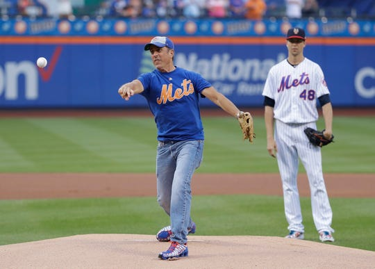 Comedian Jerry Seinfeld throws out a ceremonial first pitch as New York Mets starting pitcher Jacob deGrom, right, watches before the team's game against the Philadelphia Phillies on Friday, July 5, 2019, in New York.