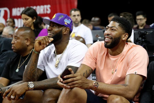 Los Angeles Laker players LeBron James, center, and Anthony Davis, right, take in an NBA summer league basketball game between the New York Knicks and the New Orleans Pelicans, Friday, July 5, 2019, in Las Vegas.