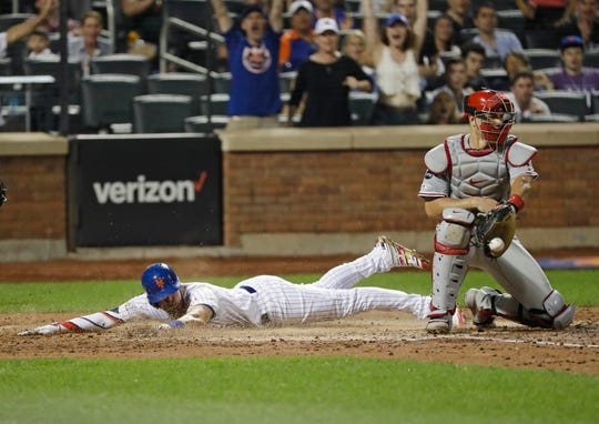 New York Mets' Jeff McNeil slides past Philadelphia Phillies catcher J.T. Realmuto to score on a double by Pete Alonso during the fifth inning of a game Friday, July 5, 2019, in New York.