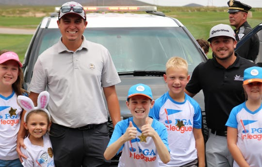 Henry Stetina, executive director of the Las Cruces Junior Golf Association, left, poses for a picture alongside PGA Jr. League players and Red Hawk assistant golf pro Matthew Sheehan during Local Heroes Day at Red Hawk Golf Course on Saturday, July 6, 2019.