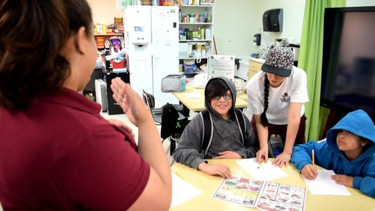 Donna Gomez, nutrition educator with New Mexico State University's Cooperative Extension Service Ideas for Cooking and Nutrition program, uses sign language to communicate with students at Albuquerque Sign Language Academy.