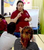 Albuquerque Sign Language Academy students Angel Ornelas, left, and Makayla Chavez-Gurule, right, receive instruction from Donna Gomez, nutrition educator with New Mexico State University's Cooperative Extension Service Ideas for Cooking and Nutrition program, through sign language, while receiving assistance from school aide Violette Bennet, middle.