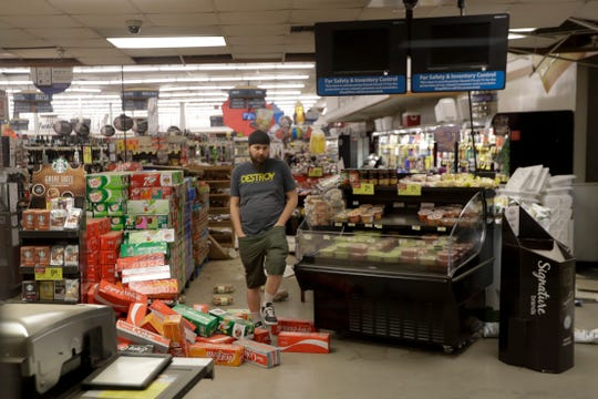 A worker steps over merchandise that is scattered on the floor of a Albertson's grocery store Saturday, July 6, 2019 following a earthquake in Ridgecrest, Calif. The Friday evening quake with a magnitude of about 7.1 jolted much of California, cracking buildings, setting fires, breaking roads and causing several injuries while seismologists warned that large aftershocks were expected to continue for days, if not weeks. ( AP Photo/Marcio Jose Sanchez)