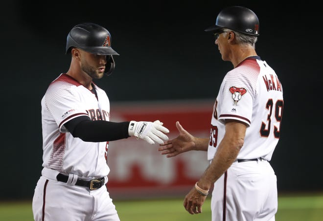 Christian Walker (53) shakes the hand of first base coach David McKay (39) during the second inning of a game against the Rockies on July 5, 2019, at Chase Field.