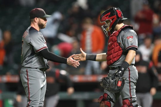 Diamondbacks closer Greg Holland and catcher Alex Avila celebrate after a victory over the Giants at Oracle Park.