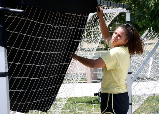 California Soccer Park employee Aurora Vasquez creates shade for one of the TVs that will show the Women's World Cup championship Sunday morning at the soccer park.