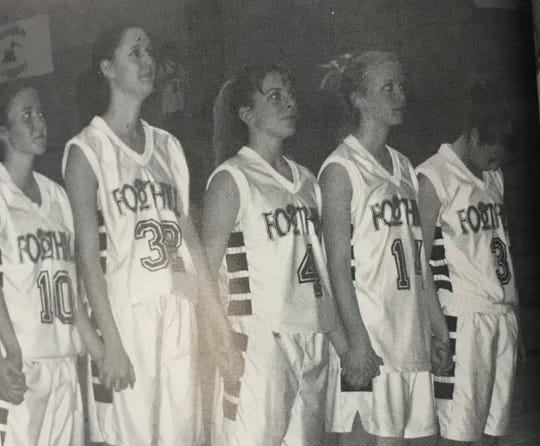 Rapinoe, far right, shuts her eyes and looks down as her basketball team listens to the national anthem before a game.
