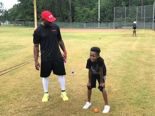 Keith Belton, associate strength and conditioning coach at the University of Kansas instructs C.J. Watkins of Greensboro, North Carolina how to run the M-drill for football during BuckMission Day on Saturday, July 6, 2019.