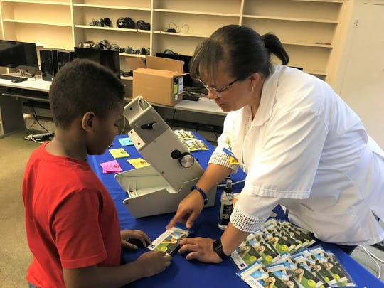Gatiti Simon (right) is a licensed optician at Walmart. She shows Christian Womack of Tallahassee some information following a free vision screening during BuckMission Day on Saturday, July, 6, 2019.