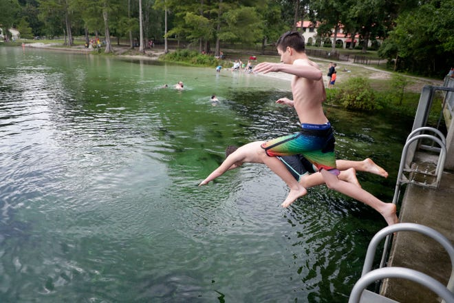 Two friends jump together into the chilly water at Wakulla Springs Saturday, July 6, 2019.