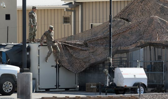 Two men wearing camouflage work to repair shade material surrounding a bank of toilets at the Clint Border Patrol Station, which is being used to house unaccompanied migrant children. The site has become the subject of much controversy and protest.