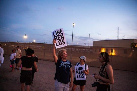 "Sue Saunders from Marin County, California, holds a sign meaning ""Free them"" in front of the Clint, Texas, facility on July 4, 2019."