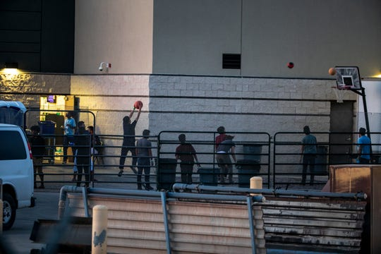 Children can be seen playing basketball July 3, 2019, from the southwest side of the U.S. Customs and Border Protection facility in Clint, Texas.