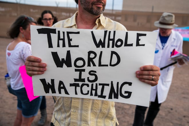 A protester holds a sign in front of the Clint, Texas, facility on July 4, 2019.