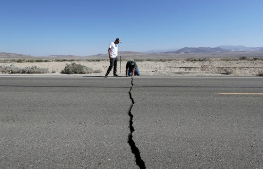 Ron Mikulaco, right, and his nephew, Brad Fernandez, examine a crack on July 6 caused by an earthquake on Highway 178 outside of Ridgecrest.