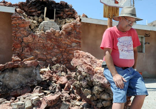 Bill Harvey contemplates what it will take to rebuild his stone fireplace after the damage it sustained in the earthquake that hit Trona on July 5, 2019.