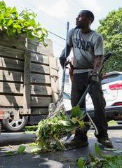 "George Wright cleans up after pruning a tree at a customer's home near New Castle Friday. Wright owns his own landscaping service after taking part in the Delaware Center for Horticulture's ""Branches to Chances"" job training program."