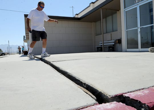 Bernard Brush steps over a new crack from the 7.1 M quake on Friday near the Old Guest House Museum in Trona, Calif. on Saturday July 6, 2019.