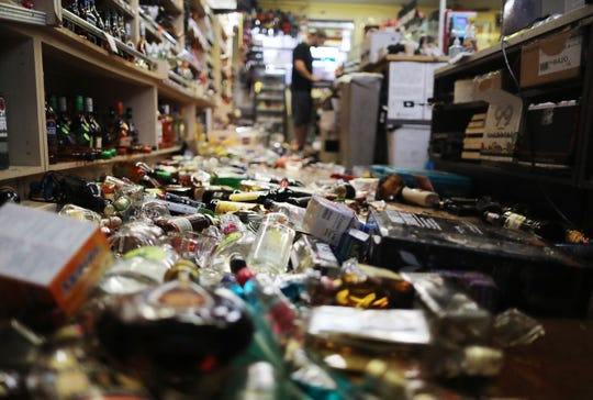 An employee works at the cash register near broken bottles scattered on the floor, following a 7.1 magnitude earthquake which struck nearby Friday in Ridgecrest, California.