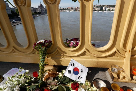 Flowers and flag of South Korea are laid on the Margit Bridge where a sightseeing boat capsized in Budapest, Hungary. Hungarian police say a South Korean woman recovered from the Danube River has been identified as the 27th fatality of the May 29 crash between a tour boat and a cruise ship.