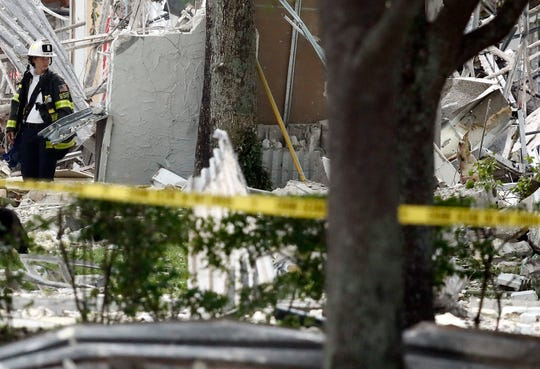 A firefighter looks at the remains of a building after an explosion on Saturday, July 6, 2019, in Plantation, Fla.