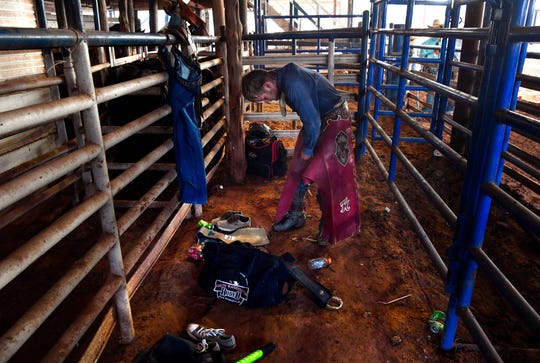 Tim Murphy of White City secures his chaps to his legs while waiting for the rodeo to begin Wednesday. Murphy was competing in the first event of the evening at Stamford's Texas Cowboy Reunion, bareback riding