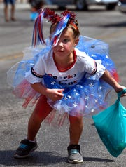 Evalyn Key, 5, of Kermit, dashes back from the street after retrieving candy during Wednesday's Texas Cowboy Reunion parade in Stamford. Evalyn was in town visiting her grandmother Connie Childress for the holiday.