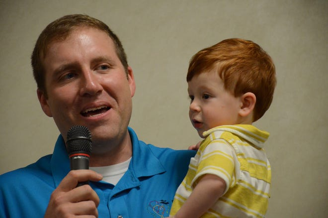 Steve Mitchell and his son, Grayson, 1, speaks at the awards banquet.