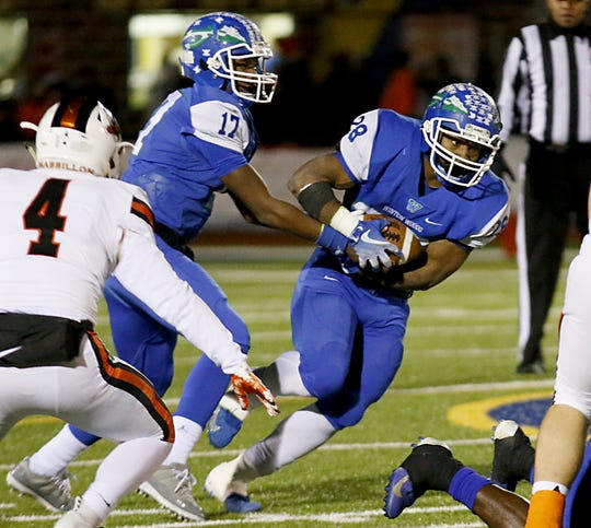 Winton Woods quarterback Michale Wingfield hands off to running back Miyan Williams during their Division II state semifinal against Massillon Washington at Gahanna Friday, Nov. 23, 2018.