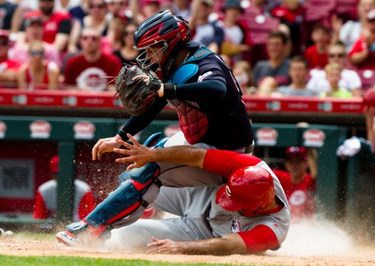 Cincinnati Reds second baseman Jose Peraza (9) slides under Cleveland Indians catcher Roberto Perez (55) home to score a runin the fifth inning of the MLB game between Cincinnati Reds and Cleveland Indians on Sunday, July 7, 2019, at Great American Ball Park in Cincinnati.