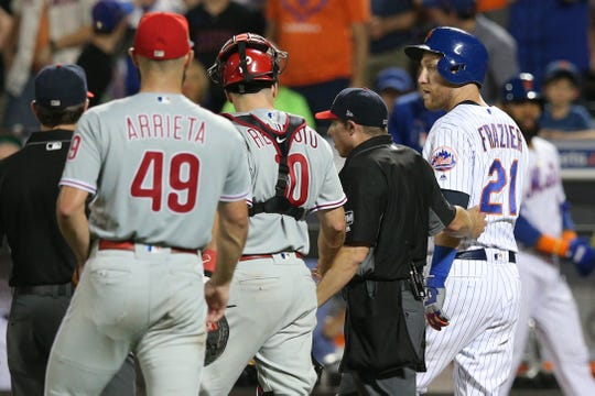 New York Mets third baseman Todd Frazier (21) is escorted to first base by home plate umpire Tripp Gibson (73) and Philadelphia Phillies catcher J.T. Realmuto (10) after being hit by a pitch by Phillies starting pitcher Jake Arrieta (49) during the fifth inning at Citi Field.