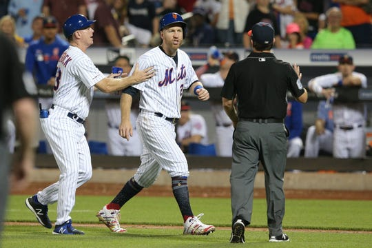 Jul 6, 2019; New York City, NY, USA; New York Mets third baseman Todd Frazier (21) is restrained by first base coach Glenn Sherlock (53) as he argues with first base umpire Chris Guccione (68) after being hit by a pitch by Philadelphia Phillies starting pitcher Jake Arrieta (not pictured) during the fifth inning at Citi Field. Mandatory Credit: Brad Penner-USA TODAY Sports