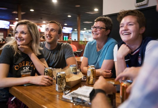 From left, Zoe Beckett, 25, of Livonia, Brandon Armstrong, 26, Cris Beckett, 50, and Claire Beckett, 22, of Farmington Hills gather for a Team USA USWNT watch party at the Detroit City Clubhouse on Sunday.