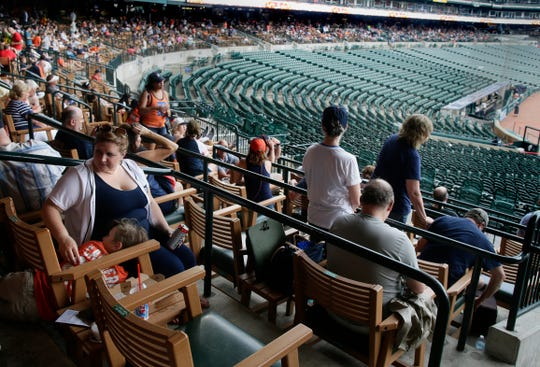 Fans abandon the open seats and wait out a rain delay for the Tigers game against the Red Sox under the upper deck at Comerica Park on July 6, 2019.
