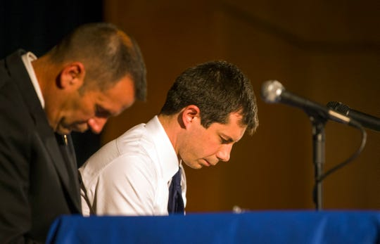 In this June 23, 2019 photo, Democratic presidential candidate and South Bend Mayor Pete Buttigieg, right, and South Bend Police Chief Scott Ruszkowski, left, bow their heads in prayer during a town hall community meeting at Washington High School in South Bend, Ind.