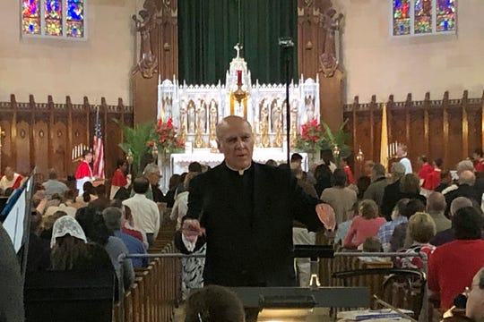 Pastor Eduard Perrone conducts a choir during Mass at Assumption of the Blessed Virgin March Parish in Detroit on June 9.