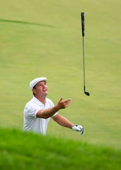 Bryson DeChambeau celebrates by tossing his club after barely clearing the water on the 14th hole during the third round of the 3M Open golf tournament Saturday in Blaine, Minn.