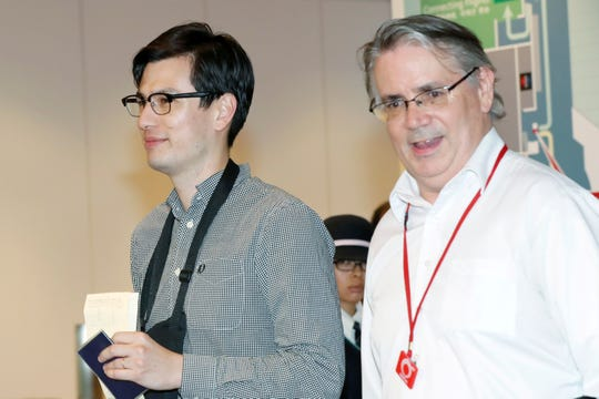In this July 4, 2019 photo, Australian student Alek Sigley, left, is escorted as he arrives at the airport in Tokyo.