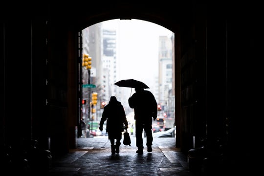 In this Feb. 12, 2019, file photo pedestrians pass beneath City Hall in Philadelphia. Nearly one-quarter of Americans say they never plan to retire, according to a poll that suggests a disconnect between individual's retirement plans and the realities of aging in the workforce.