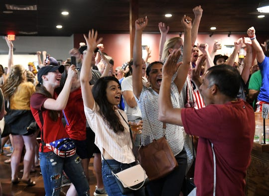 Soccer fans, from right, Sudheer Ummadi, his wife, two arms up, Vinaya Ummadi, both of Bloomfield Hills, with their cousin, long hair with arm up, Ruchi Bisen of Cleveland, cheer after US team scores their first goal the U.S. Women play in the World Cup Final game at the Detroit City Football Club Fieldhouse in Detroit on July 7, 2019. (Robin Buckson / The Detroit News)