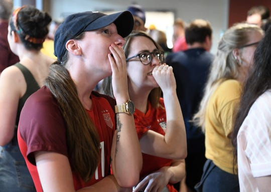 Emily Cossins, left, 22, of Taylor and Allison McWilliams, 24, of Detroit react to a play while watching the U.S. Women play in the World Cup Final game at the Detroit City Clubhouse on Sunday.